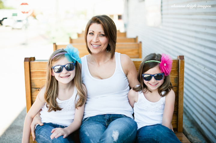 A mother and her daughters in white tank tops, jeans, and bright colored flower headbands with mirrored sunglasses in Grapevine, Texas.