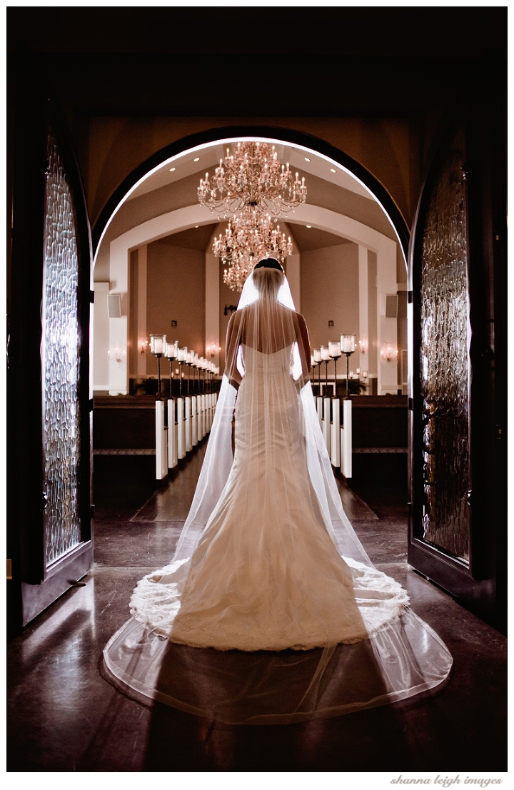 Jennifer walking through the doors of the chapel for her bridal portraits at her gorgeous mediterranean style wedding venue, the Piazza in the Village in Colleyville, Texas.