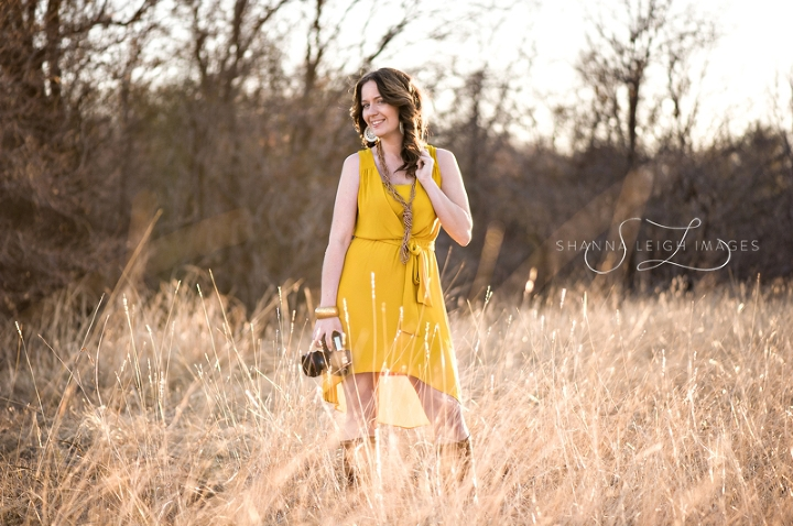 A photographer posing with her Canon camera in a mustard colored dress with Frye Jane boots in an overgrown field.