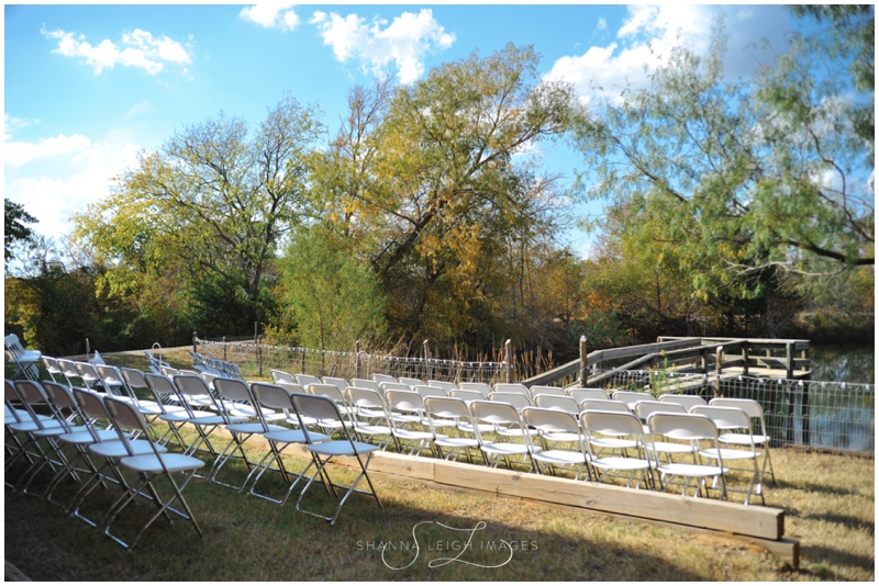 White chairs set up in front of the water before an outdoor wedding ceremony at Wildscape Ranch in Mansfield, Texas.